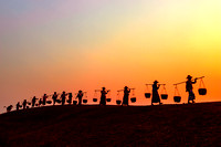 Villagers walking home at sunset.
